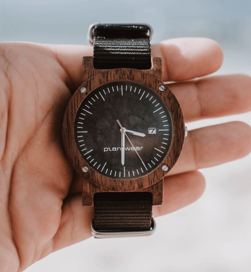 wooden watch with brown crown and black strap