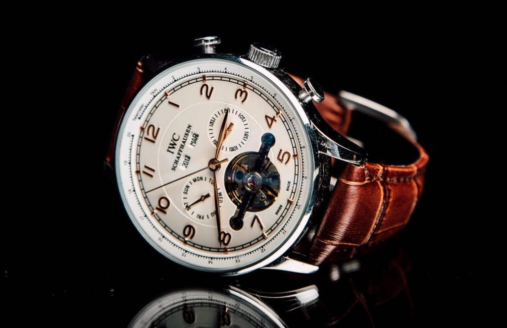 A white-dial watch with movement visible through a cut