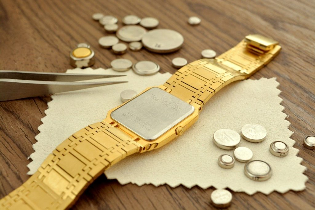 loads of quartz watch batteries around a golden watch