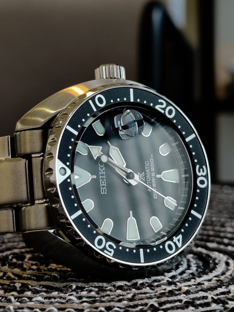Metallic diver's watch with rotating bezel and domed crystal
