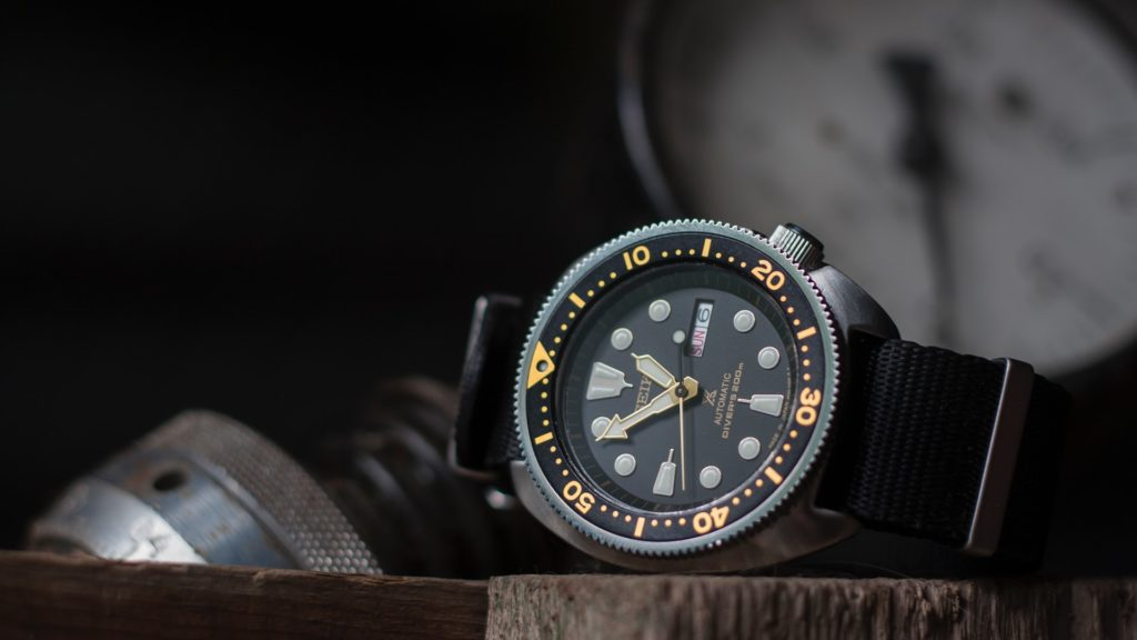 Analog watch with rotating bezel and yellow markings