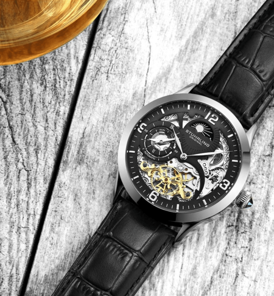 Stuhrling skeleton watch on a grey wooden table